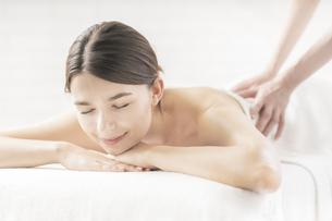 明るい雰囲気のエステサロンでマッサージを受ける若い女性の写真素材 [FYI04862218]