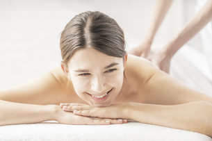 明るい雰囲気のエステサロンでマッサージを受ける若い女性の写真素材 [FYI04862221]