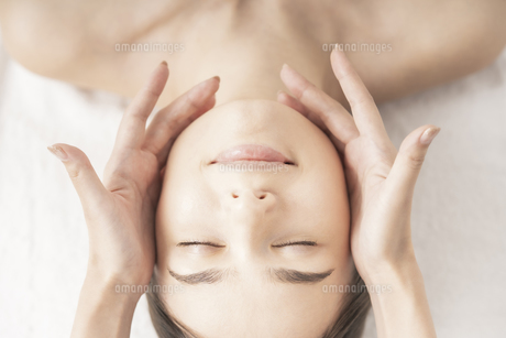 エステサロンで頭部をマッサージされる若い女性の写真素材 [FYI04862230]