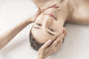 エステサロンで頭部をマッサージされる若い女性の写真素材 [FYI04862233]