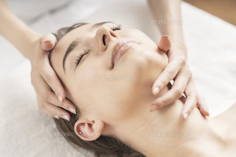 エステサロンで頭部をマッサージされる若い女性の写真素材 [FYI04862234]