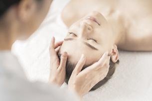 エステサロンで頭部をマッサージされる若い女性の写真素材 [FYI04862237]