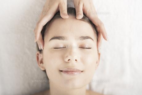 エステサロンで頭部をマッサージされる若い女性の写真素材 [FYI04862238]