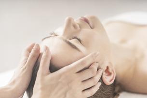 エステサロンで頭部をマッサージされる若い女性の写真素材 [FYI04862239]