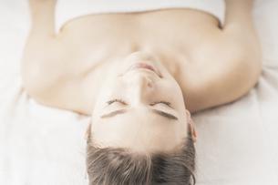 明るい雰囲気のエステサロンでベッドに横になる若い女性の写真素材 [FYI04862264]