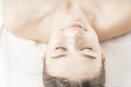 明るい雰囲気のエステサロンでベッドに横になる若い女性の写真素材 [FYI04862265]