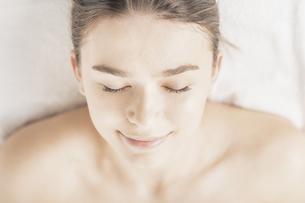 明るい雰囲気のエステサロンでベッドに横になる若い女性の写真素材 [FYI04862266]