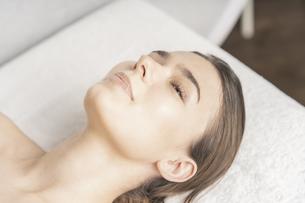 明るい雰囲気のエステサロンでベッドに横になる若い女性の写真素材 [FYI04862267]