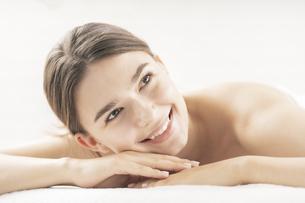 明るい雰囲気のエステサロンでベッドに横になる若い女性の写真素材 [FYI04862268]