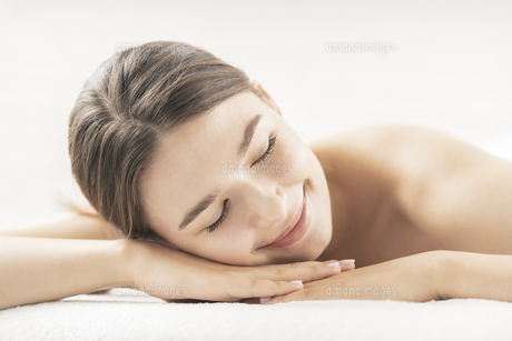 明るい雰囲気のエステサロンでベッドに横になる若い女性の写真素材 [FYI04862269]