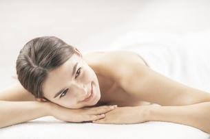 明るい雰囲気のエステサロンでベッドに横になる若い女性の写真素材 [FYI04862271]