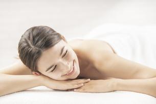 明るい雰囲気のエステサロンでベッドに横になる若い女性の写真素材 [FYI04862272]