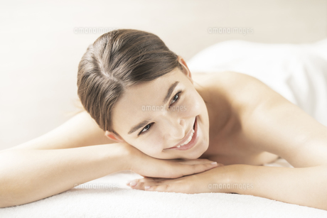 明るい雰囲気のエステサロンでベッドに横になる若い女性の写真素材 [FYI04862273]