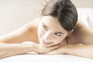 明るい雰囲気のエステサロンでベッドに横になる若い女性の写真素材 [FYI04862274]