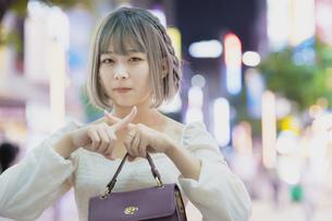 夜の繁華街で、NGサインをする女性の写真素材 [FYI04862286]