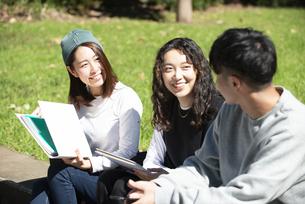 外でノートを広げて話している学生3人の写真素材 [FYI04862580]
