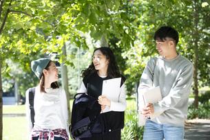 笑いながら話をしている大学生3人の写真素材 [FYI04862584]