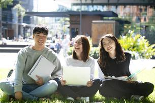外でパソコンを開いて笑っている学生3人の写真素材 [FYI04862601]