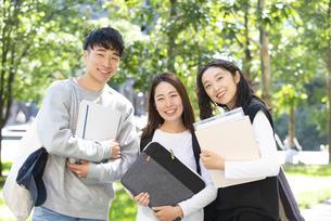 ノートを抱えて笑っている学生3人の写真素材 [FYI04862602]