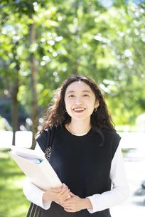 ノートを抱えて笑っている女子学生の写真素材 [FYI04862605]