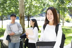 パソコンポーチを持って笑っている女子学生の写真素材 [FYI04862611]