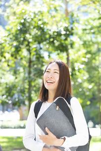 パソコンポーチを持って笑っている女子学生の写真素材 [FYI04862612]