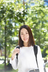 緑をバックにこちらを見ている女子学生の写真素材 [FYI04862614]