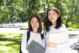 ファイルを抱えて笑っている女子学生2人の写真素材 [FYI04862617]