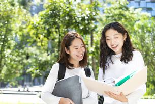 ファイルを広げて話している女子学生2人の写真素材 [FYI04862619]