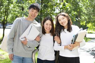 ファイルを抱えて笑っている学生3人の写真素材 [FYI04862620]