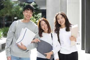 ファイルを抱えて笑っている学生3人の写真素材 [FYI04862628]