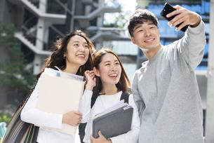 笑顔でセルフィーをしている学生3人の写真素材 [FYI04862629]