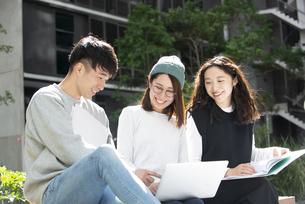 ファイルを広げて話している学生3人の写真素材 [FYI04862642]
