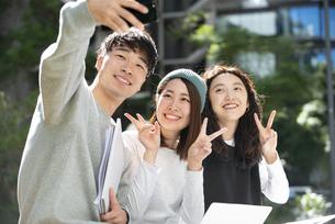 笑顔でセルフィーをしている学生3人の写真素材 [FYI04862643]