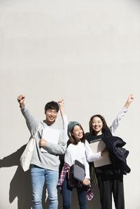 壁の前でポーズをしている学生3人の写真素材 [FYI04862654]