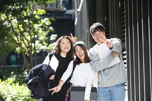 笑顔でポーズをとっている学生3人の写真素材 [FYI04862656]