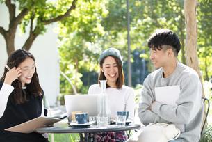 カフェで勉強をしている学生3人の写真素材 [FYI04862668]