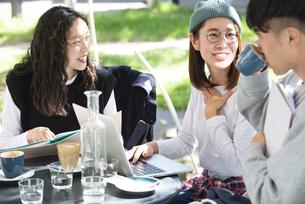カフェで勉強をしている学生3人の写真素材 [FYI04862672]