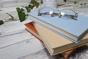 テーブルの上の本とメガネの写真素材 [FYI04863203]