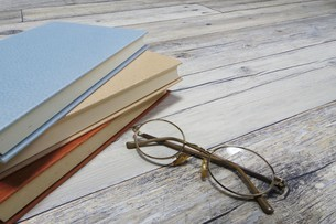 テーブルの上の本とメガネの写真素材 [FYI04863204]