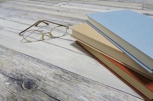 テーブルの上の本とメガネの写真素材 [FYI04863205]