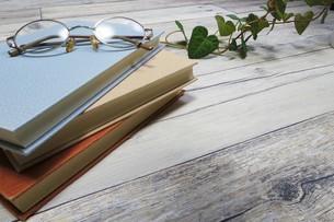 テーブルの上の本とメガネの写真素材 [FYI04863206]