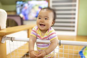 つかまり立ちで笑顔の赤ちゃんの写真素材 [FYI04863375]