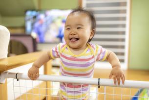 つかまり立ちで笑顔の赤ちゃんの写真素材 [FYI04863376]