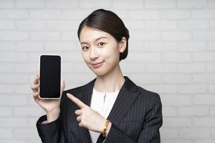 スマートフォンを操作するビジネスウーマンの写真素材 [FYI04863816]