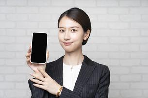 スマートフォンを操作するビジネスウーマンの写真素材 [FYI04863825]