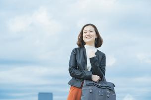 空を見上げるカジュアルな服装のビジネスウーマンの写真素材 [FYI04863826]