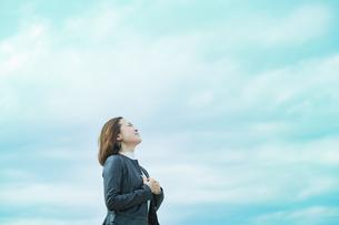 空を見上げるカジュアルな服装のビジネスウーマンの写真素材 [FYI04863831]