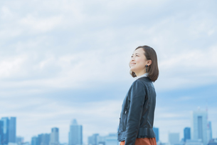 空を見上げるカジュアルな服装のビジネスウーマンの写真素材 [FYI04863836]