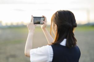 スマートフォンで景色を撮影するアジア人女性の高校生の写真素材 [FYI04863837]